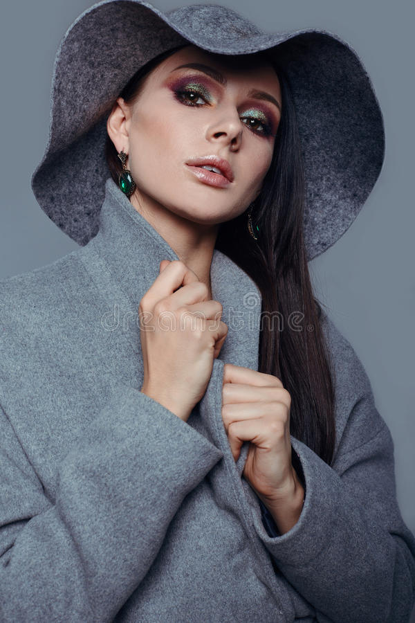 Young fashion brunette woman beauty in gray coat and hat. Young fashion brunette woman beauty portrait posing in studio wearing in gray coat and hat royalty free stock images