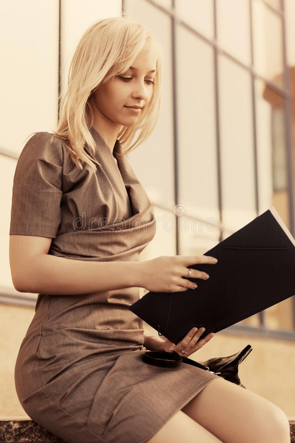 Young fashion business woman with file folder at office building royalty free stock image