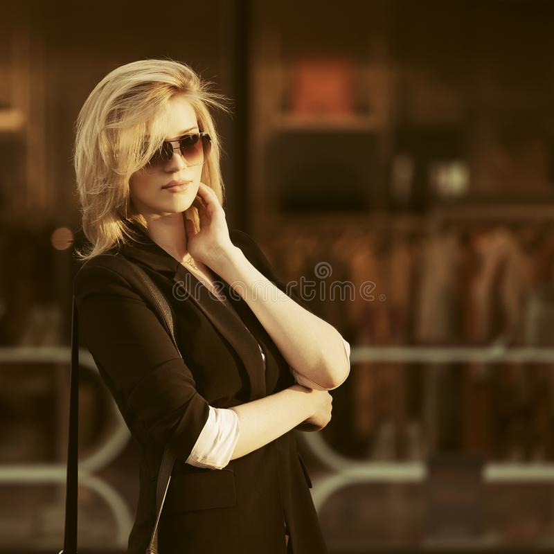 Young fashion business woman in sunglasses against window display royalty free stock photos