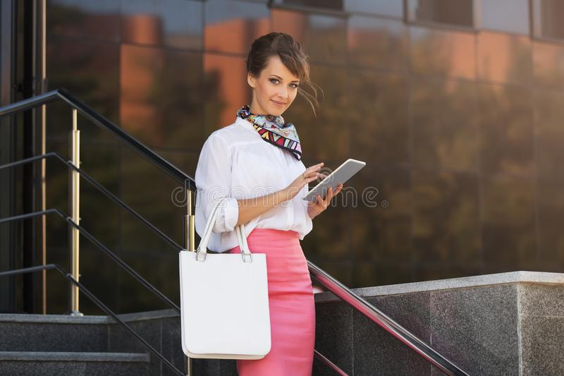 Young fashion business woman using digital tablet computer at office building. Stylish female model wearing white shirt and pink pencil skirt stock image