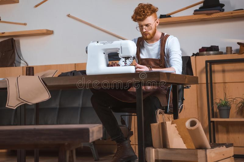 young fashion designer in apron and eyeglasses working with sewing machine stock photography
