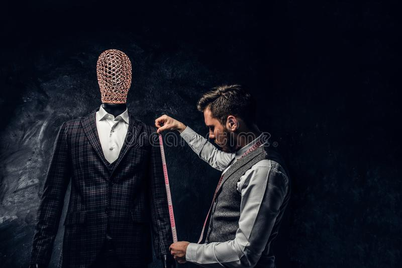 A fashion designer with a measuring tape check the length of the sleeves of a custom made elegant men`s suit in a dark stock images