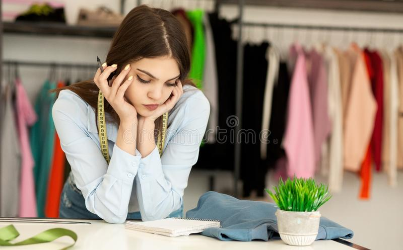 Young Fashion Designer Planning Budget For New Clothing Collection. Budgeting For Fashion Startup. Clothes Designer Planning Financials For Own Showroom. Free royalty free stock photo