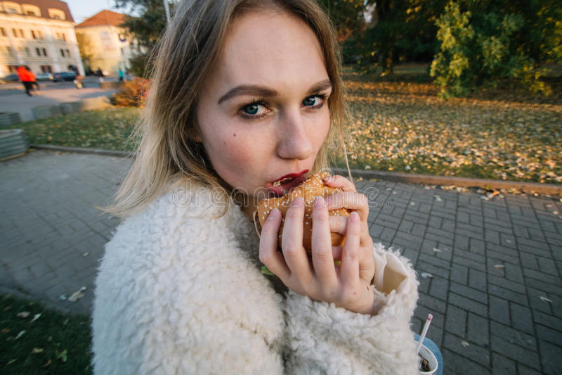 Young fashion funny woman eating hamburger outdoor on the street.  royalty free stock photo