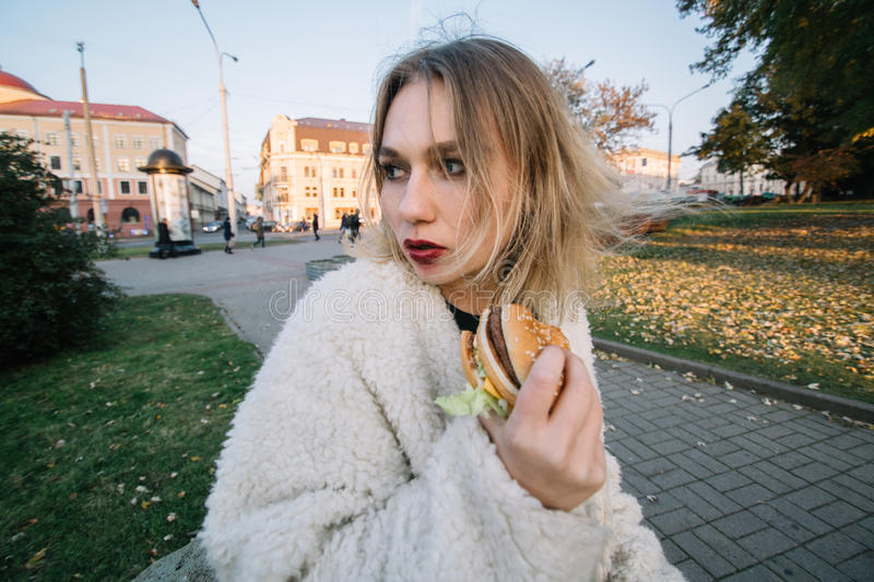 Young fashion funny woman eating hamburger outdoor on the street.  royalty free stock photography