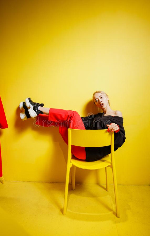 Young fashion girl blogger dressed in red trousers and black jacke possing sitting on the stool in the room with yellow stock image