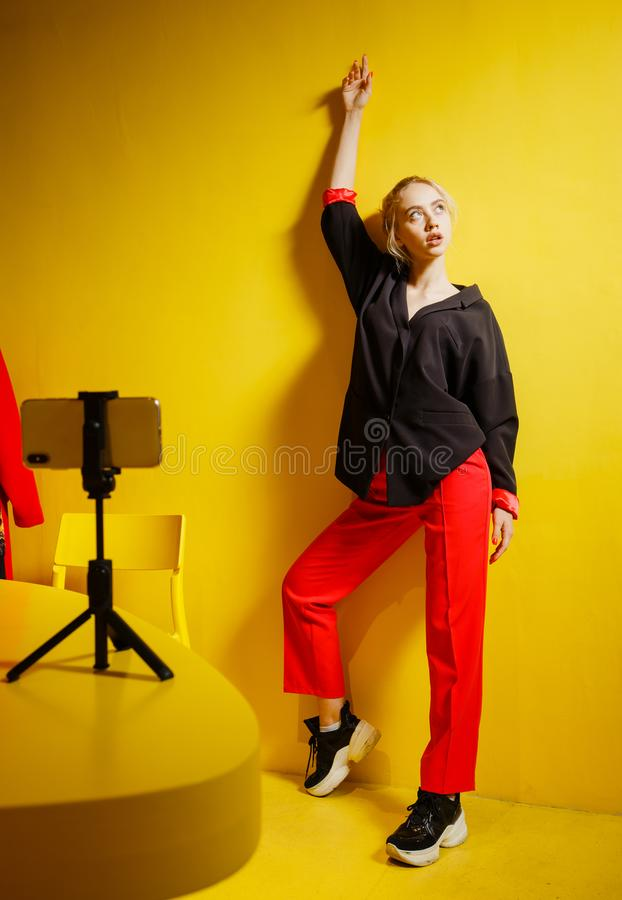 Young fashion girl blogger dressed in red trousers and black jacket takes a selfie on the smartphone standing on a stand stock photo