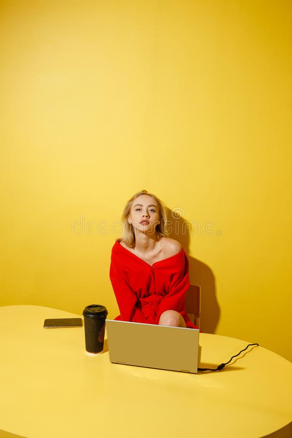 Young fashion girl blogger dressed in stylish red coat sitting at the yellow table with the laptop and cup of coffee on stock image