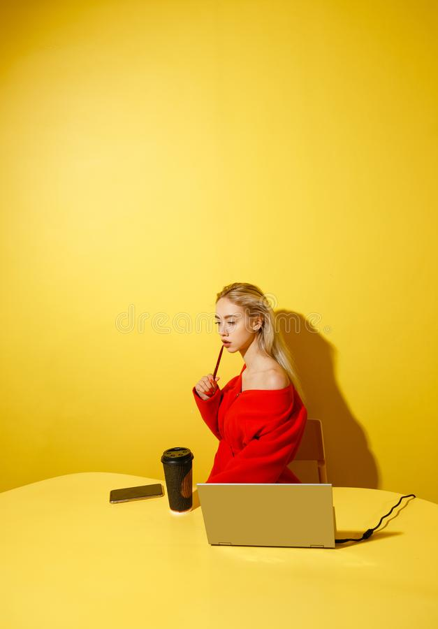 Young fashion girl blogger dressed in stylish red coat sitting at the yellow table with the laptop and cup of coffee on royalty free stock images