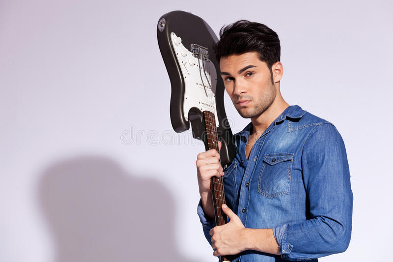 Young fashion guitarist. Holding his guitar near head on gray background royalty free stock photos