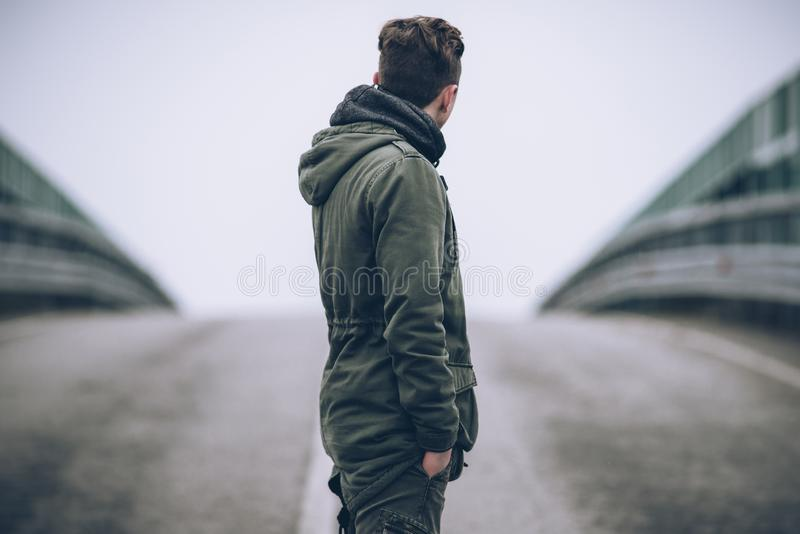 Young fashion guy standing in the center of an empty road stock photos