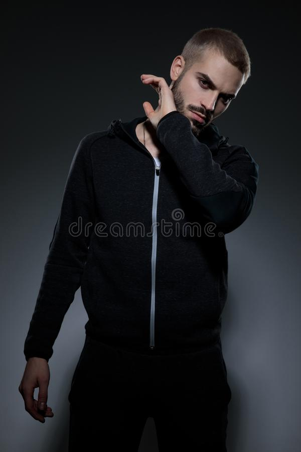 Young fashion guy wearing gym suit and touching beard. Young fashion guy wearing gym suit, holding hands and touching beard, standing  on grey background stock photos