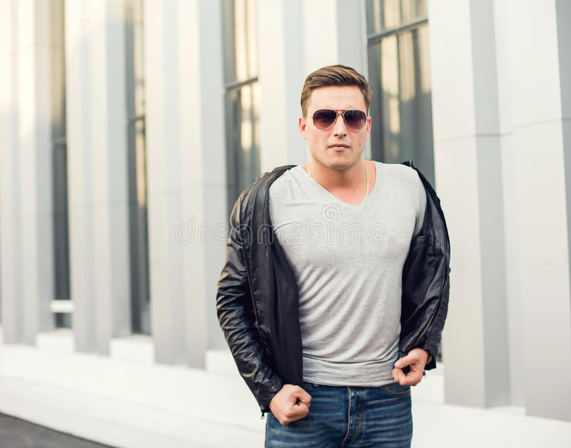 Young, fashion man in black leather jacket, sunglasses and jeans. Outdoor portrait. Young, fashion man in black leather jacketm sunglasses and jeans. Outdoor royalty free stock photography
