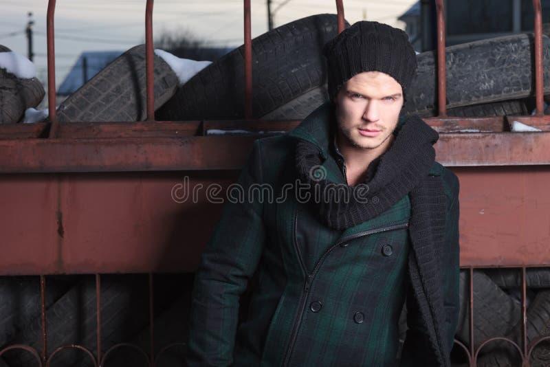 Young fashion man poses near car tires stock photo