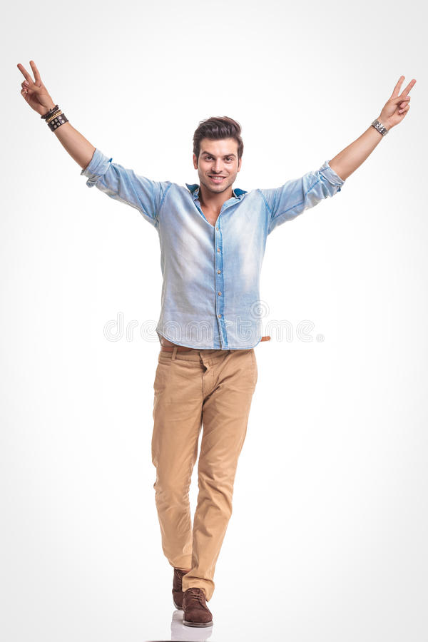 Young fashion man walking while showing the victory sign. royalty free stock photo
