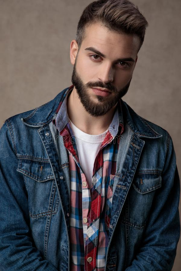 Young fashion man wearing blue denim jacket on brown background royalty free stock photo