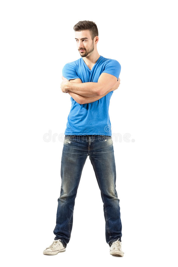 Young fashion model with arms wrapped around him looking away. Young fashion model with arms wrapped around himself looking away. Full body length isolated over royalty free stock photography