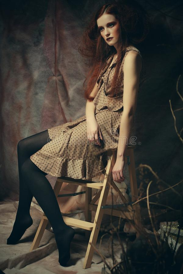 Young fashion model with creative make up sitting on a stool in stock photo