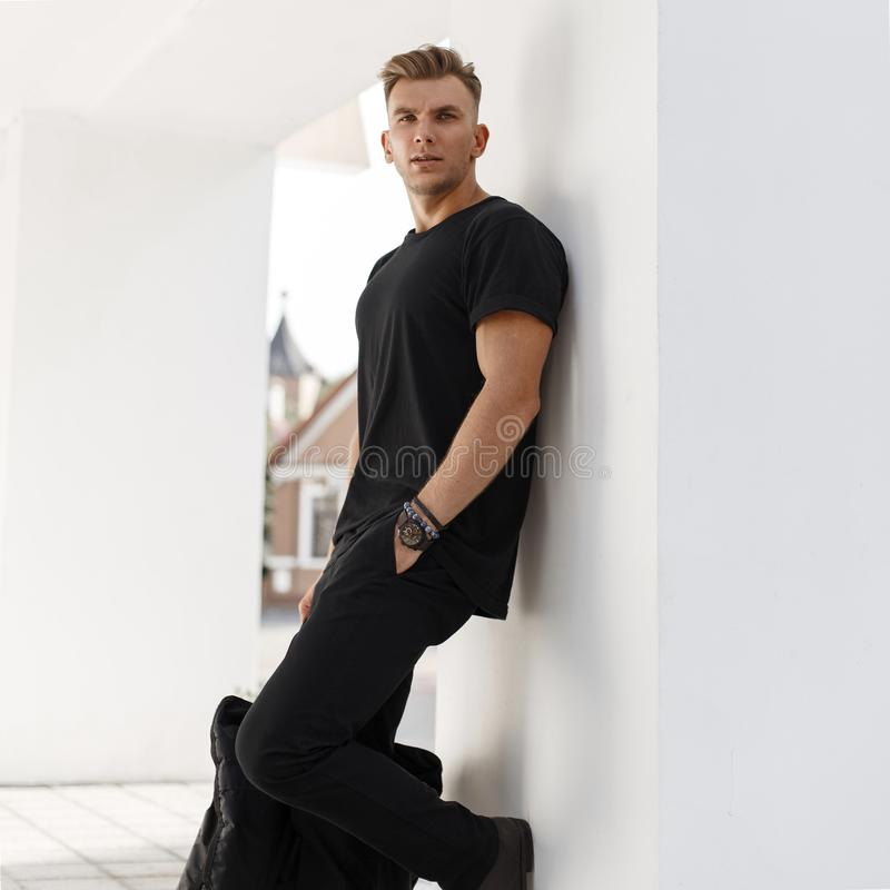 Young fashion model man with bag in black shirt stock photography