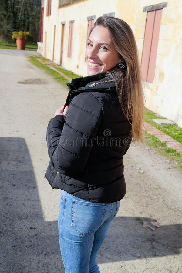 Young fashion slim woman blond in black jacket walking in city street rear behind view stock images
