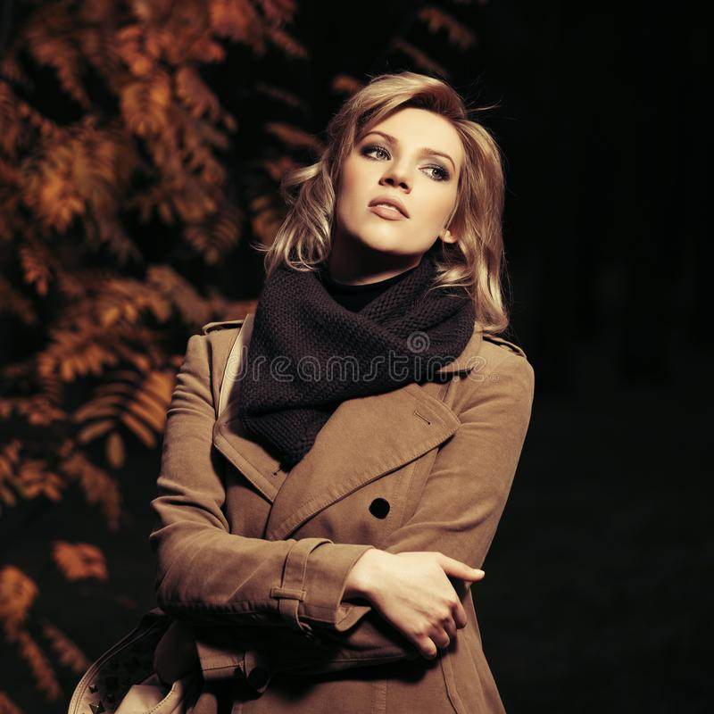 Young fashion woman in beige coat walking in autumn city park at night. Young fashion woman walking in autumn city park at night Stylish female model wearing royalty free stock photos