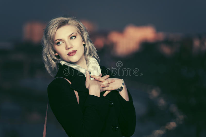 Young fashion woman in black coat walking in a night street stock image