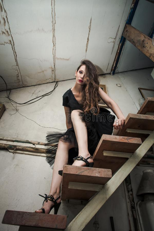 Young fashion woman in black dress in old artist studio on stair stock photography