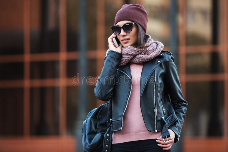 Young fashion woman in black leather jacket using cell phone in city street royalty free stock photos