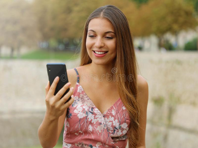 Young fashion woman doing video call outdoor stock photo