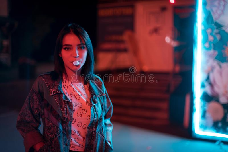 Young fashion young woman in fur glasses blowing bubble gum illuminated with street neon blue pink sign stock image