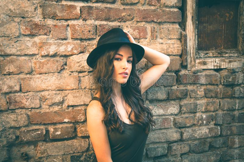 Young fashion woman with hat stand in front old abandoned house royalty free stock photography