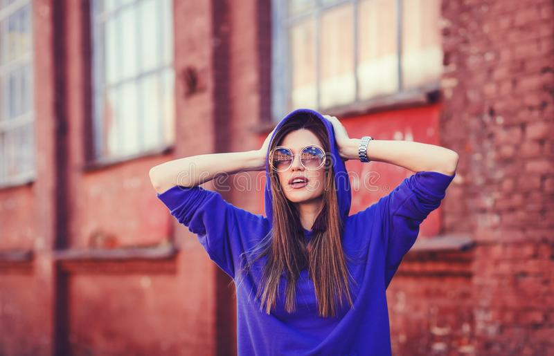 Young fashion woman posing on the background of red wall royalty free stock photography