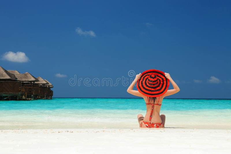 Young fashion woman relax on the beach. Happy lifestyle. White sand, blue sky and crystal sea of tropical beach. Vacation. At Paradise. Ocean beach relax stock images