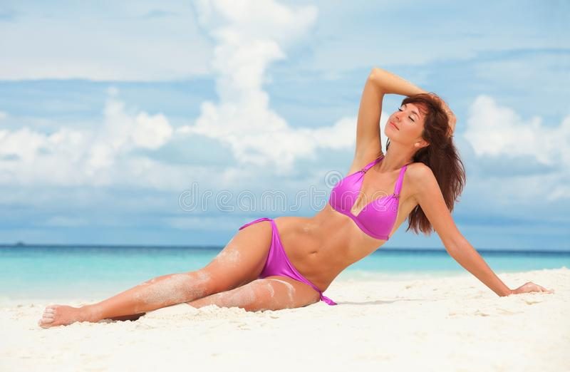 Young fashion woman relax on the beach. Happy lifestyle. White sand, blue sky and crystal sea of tropical beach. Vacation at royalty free stock image