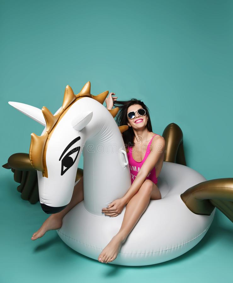 Young fashion woman relaxing with big inflatable unicorn pegasus float mattress in pink bikini for swimming pool stock images