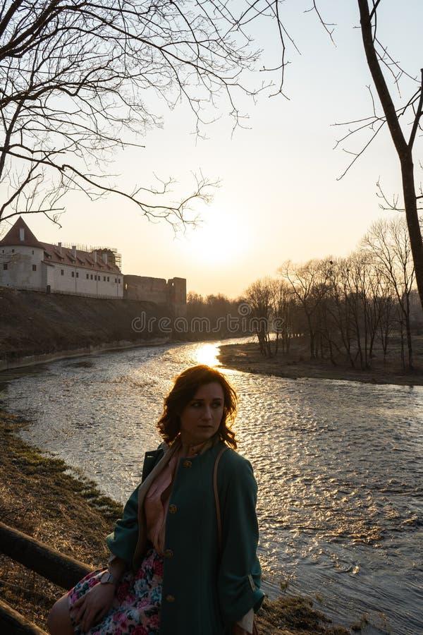 Young fashion woman relaxing and enjoying sunset near a river in Bauska, Latvia, 2019 stock image