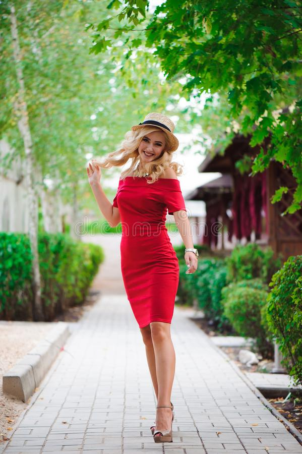 Young fashionable attractive blonde woman walking in the park royalty free stock image