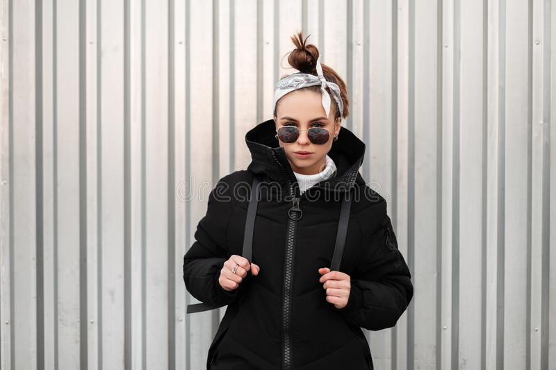 Young fashionable beautiful hipster woman with a stylish hairstyle with a bandana in black sunglasses in a long black coat. With a backpack on her shoulders royalty free stock image