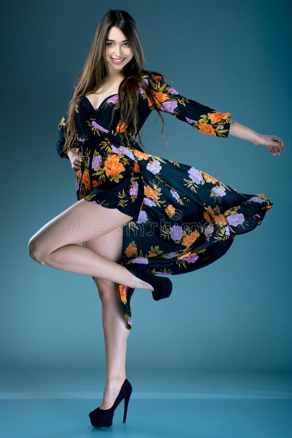 Young fashionable brunette woman in dress with floral print in high heels posing in studio. cruise collection royalty free stock image
