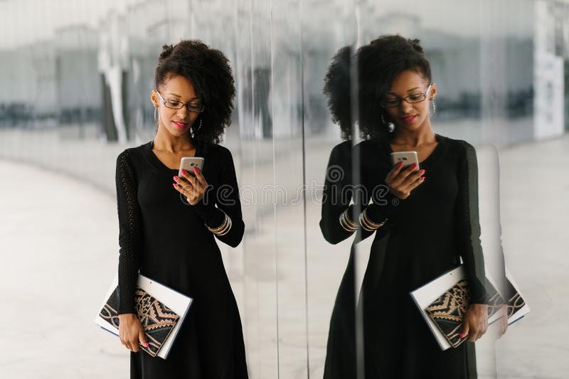 Young fashionable businesswoman using cellphone royalty free stock photos
