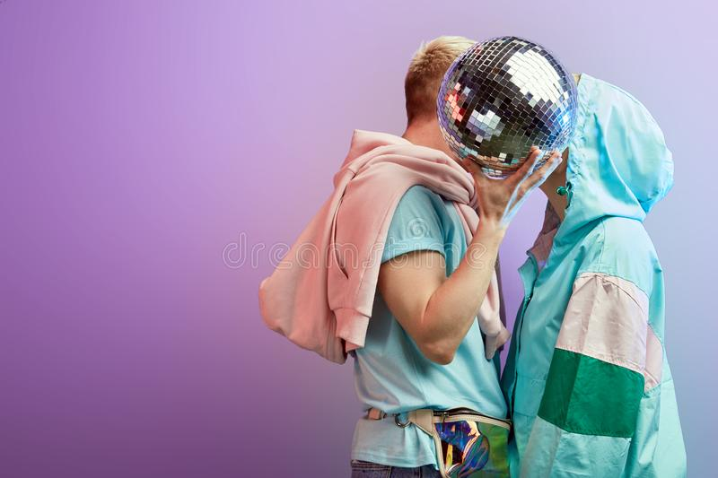 Young fashionable couple of dancers posing with disco ball on violet background stock image