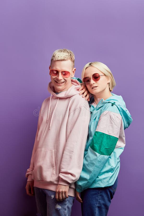 Young fashionable couple of dancers posing with disco ball on violet background royalty free stock photos