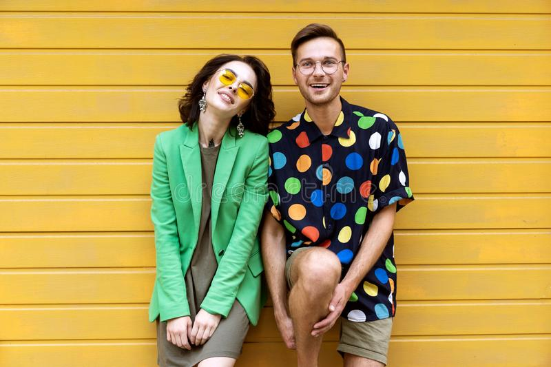 Young fashionable couple on yellow background stock image