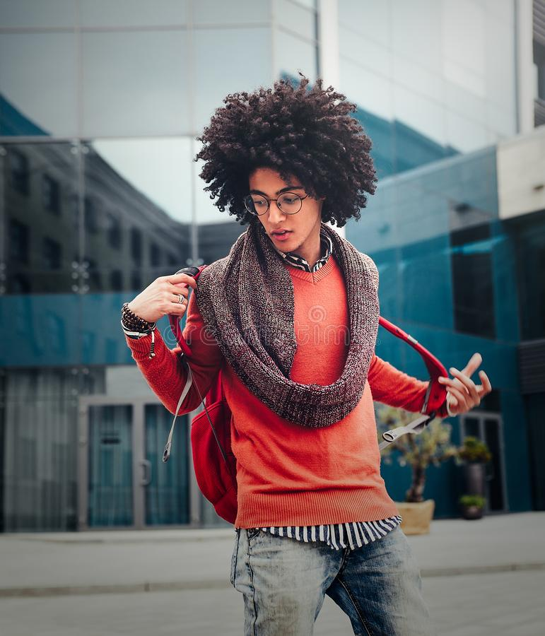 Young fashionable dressed curly guy walks through the streets against a skyscraper. A student with a backpack standing against the background of glass walls stock image