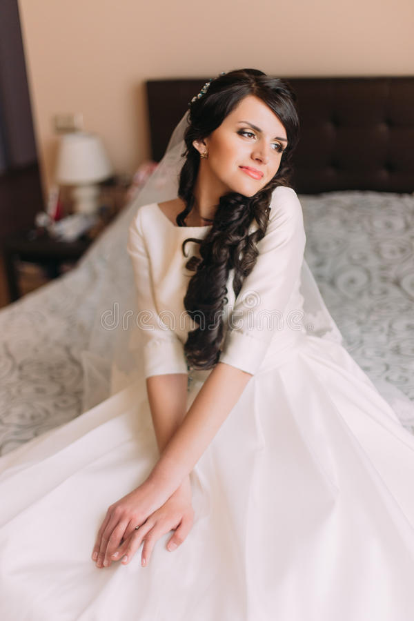 Young fashionable excited bride sitting on bed in wedding dress and dreaming of her new married life.  royalty free stock photos
