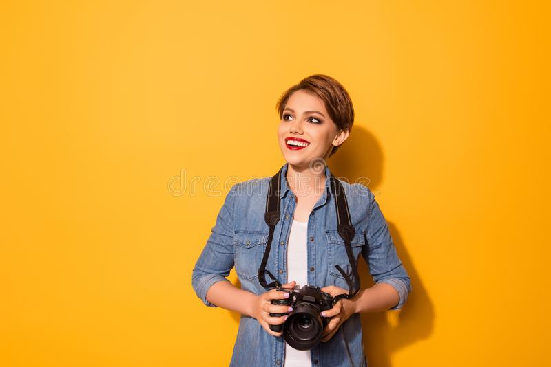 Young fashionable female photographer is smiling on the yellow b stock photos
