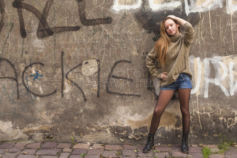 Young fashionable girl posing near the old wall. Pretty young fashionable girl posing near the old wall stock image
