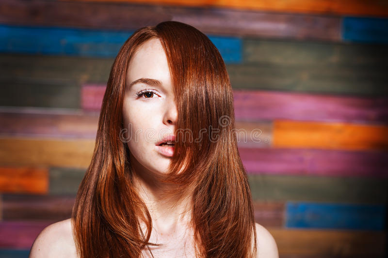 Young fashionable girl with red hair. Young beautiful fashionable girl with long red hair looking to the camera over colorful background. Hairdo style royalty free stock photography
