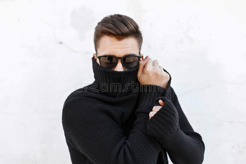 Young fashionable guy in black sunglasses vite and covers the fa. Ce with a cloth stock photos