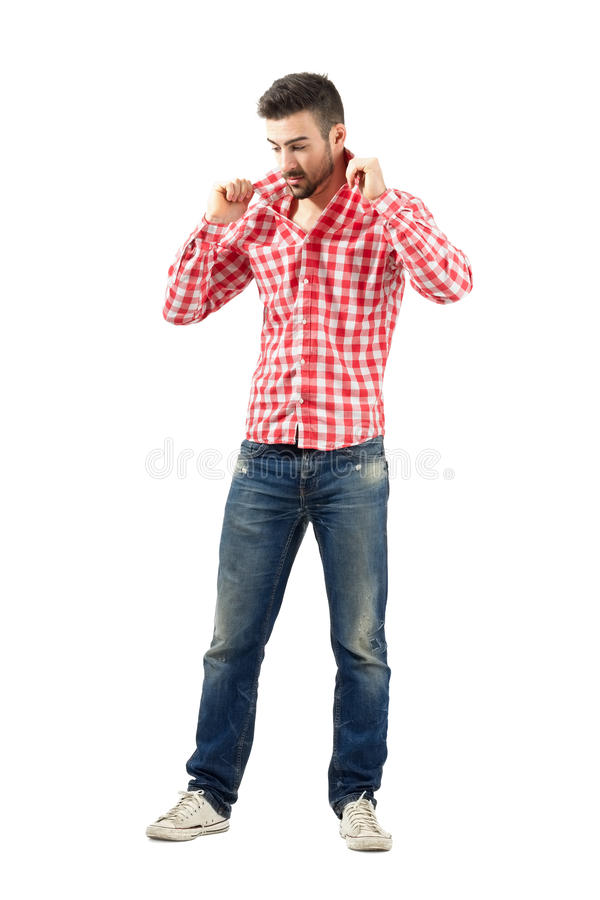 Young fashionable guy holding collar on his plaid shirt. Young fashionable guy adjusting turned up collar on his plaid shirt. Full body length portrait isolated royalty free stock images